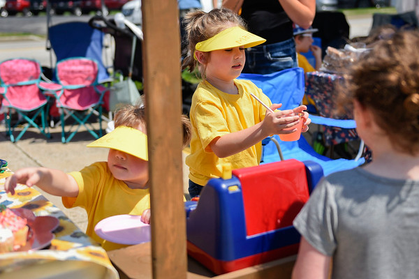 BEN MIKESELL   THE GOSHEN NEWS<br /> Marlee Nagle, 5, of Mishawaka, carries a cup of lemonade while he sister Reese, 3, left, grabs a cookie while they operate their lemonade stand Saturday afternoon at Centier Bank in Goshen.