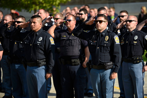 BEN MIKESELL | THE GOSHEN NEWS<br /> Goshen police officers salute the American flag during Wednesday's police officer ceremony outside of the Goshen Police Station.
