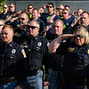 BEN MIKESELL | THE GOSHEN NEWS<br /> Goshen police officers and fire fighters, in back, salute the American flag during Wednesday's police officer ceremony outside of the Goshen Police station.