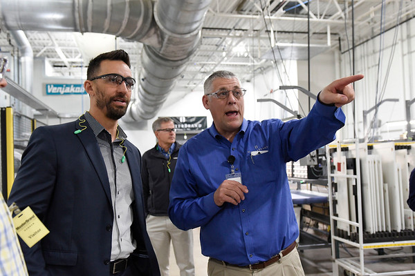 BEN MIKESELL | THE GOSHEN NEWS<br /> Tim Stumph, general manager at MasterBrand Cabinets, right, shows off the new Venjakob assembly line to Goshen mayor Jeremy Stutsman during a ribbon cutting ceremony Wednesday morning at MasterBrand Cabinets in Goshen.
