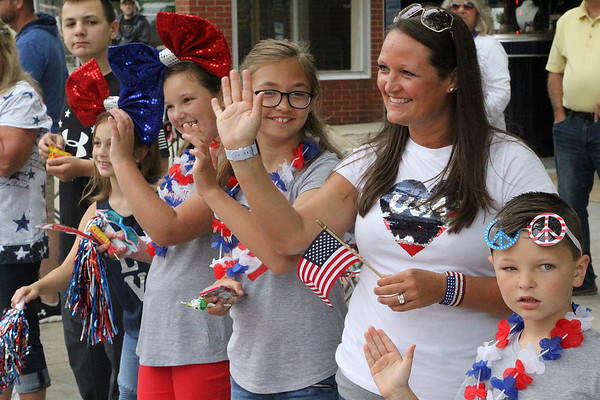 Roger Schneider | The Goshen News<br /> <br /> The Maust family of Goshen smiles and waves as the Memorial Day parade in Goshen passes by. From left are Kahler, 10, Maylin, 8, Lyla, 9, Izzi, 11, Brooke and Lain Maust, 6.