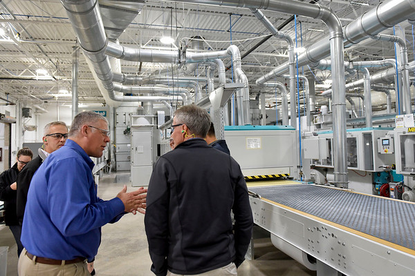 BEN MIKESELL | THE GOSHEN NEWS<br /> Tim Stumph, general manager at MasterBrand Cabinets, left, shows off the new Venjakob assembly line during a ribbon cutting ceremony Wednesday morning at MasterBrand Cabinets in Goshen.