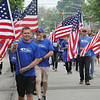 Roger Schneider | The Goshen News<br /> Jim Brown of New Paris leads the Grace Community Church's flag group down Main Street in Goshen during the annual Memorial Day parade.