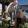BEN MIKESELL | THE GOSHEN NEWS<br /> Branden Hochstetler, of Nappanee, places his dog sculpture named Harley in a flower bed Wednesday evening in downtown Nappanee.