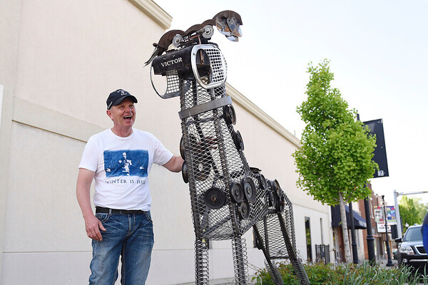 BEN MIKESELL | THE GOSHEN NEWS<br /> Jeff Stillson, president of the Nappanee Arts Council, stands with one of his three creations, a Great Dane made out of lawn mower and other metal parts, which was installed Wednesday afternoon along Main Street in Nappanee. Local artists created 18 dogs made from scrap metal for this year's project, called Junkyard Dog Sculptures.