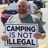 "JOHN KLINE | THE GOSHEN NEWS<br /> Goshen minister Michael Nettrouer holds up a sign reading ""Camping Is Not Illegal"" during a rally advocating for the city's homeless population in downtown Goshen Saturday afternoon."