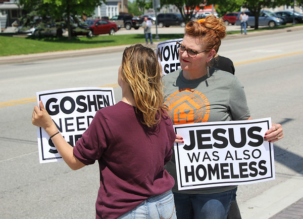 "JOHN KLINE | THE GOSHEN NEWS<br /> Julie Kramer, founder of the Goshen-based homeless advocacy nonprofit Operation Treehouse, right, holds up a sign reading ""Jesus Was Also Homeless"" while chatting with attendees during a rally advocating for the city's homeless population in downtown Goshen Saturday afternoon."