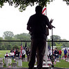 Roger Schneider | The Goshen News<br /> Featured speaker at Goshen's Memorial Day service at Oakridge Cemetery, Harold Eichhorn, is silhouetted on the lectern as attendees listen to his story of serving two tours overseas with the National Guard and his struggles with depression and PTSD since returning.