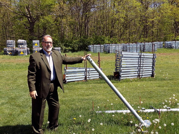 THE GOSHEN NEWS | Denise Fedorow<br /> Wawasee Community Schools Superintendent Thomas Edington holds up a pole that will be part of the framework for a solar system array behind the transportation building. In the background are stacks of solar panels. The school corporation is converting all its buildings to solar energy.
