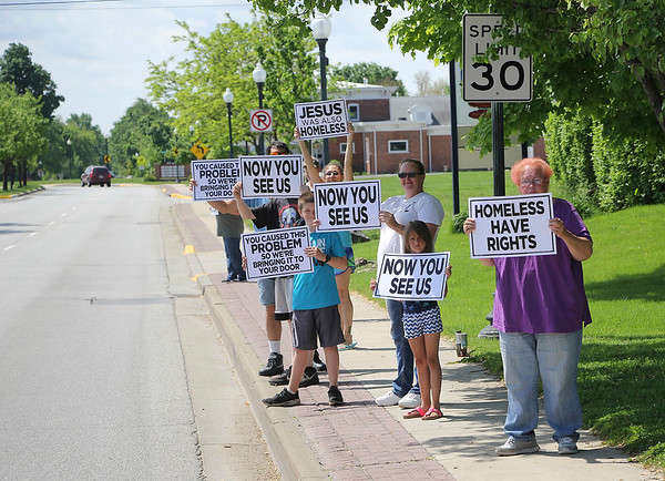 JOHN KLINE | THE GOSHEN NEWS<br /> A group of homeless citizens, their advocates and supporters line the 200 block of Third Street Saturday afternoon during a rally advocating for the city's homeless population, some of whom are facing a removal deadline for their camp along the Goshen millrace.