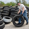 BEN MIKESELL | THE GOSHEN NEWS<br /> Chris Barrick, Goshen, rolls a tire into the pile of rubber set to be recycled Thursday during Beautify Goshen Week at the Goshen Street Department.