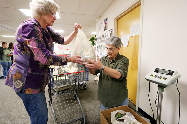 AIMEE AMBROSE | THE GOSHEN NEWS <br /> (from left) Carol Simmons, Goshen, hands a bag of donated food to Jim Froelich, Goshen, to be weighed at the Salvation Army, 1013 N. Main St., in Goshen. The two were among the volunteers who helped during the annual Stamp Out Hunger food drive Saturday.