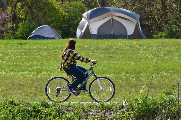 BEN MIKESELL | THE GOSHEN NEWS<br /> A bicyclist drives past the rows of tents Wednesday evening along the Mill Race Trail in Goshen. The city announced a resolution on the homeless tents in Goshen, stating those camping on public property will have to relocate by May 27.