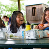 BEN MIKESELL | THE GOSHEN NEWS<br /> Hilary Ramos, 8, center, reaches for an apple while eating lunch with her sister Ashley, 9, left, and friend Leilany Escalente, 8, right, Tuesday at Shanklin Park in Goshen. The Ramos family comes to Shanklin Park every day during the summer to take advantage of the U.S. Department of Agriculture's Summer Food Service Program, which provides free meals to children 18 and younger in June and July. Meals are made throughout the week at Goshen Middle School, and the program is open to anyone age 18 or younger, regardless of where they may reside.