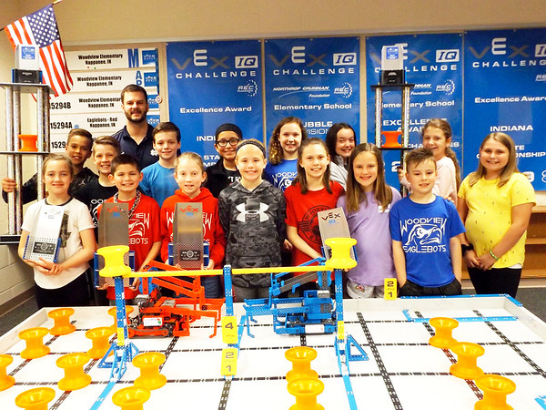 DENISE FEDOROW | THE GOSHEN NEWS<br /> The Woodview Elementary School's Eagles Robotics team members and coach are still beaming from their Indiana State championship win in March and their World Championship Excellence win last month. The large trophies in the back are from their state championship win and the smaller Vex Robotics trophies held by several students are from the Vex Robotics World Championship win. In front of the students are the robots they designed and built. The orange hubs on the field have to be picked up, driven to the edges and stacked as part of the competition.<br /> In the front row from left are: Aylah Stutzman, Tyler Frye, Elsa Jessup, Ava Zercher, Kyla Mishler, Sophie Yoder and Sebastian Chapman.<br /> In back from left are: Isaac Bell, Caleb Vincent, Coach Jake Simons, Caleb Stutzman, Tatiana Mora, Eden Wiggins, Lilly Geyer, Sophie Richmond and Olivia Wogoman. Not present for the photo was Landon Hahn.