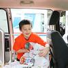 AIMEE AMBROSE | THE GOSHEN NEWS <br /> Michael Aimone loads a bag of food into a van at the Aspen Meadows apartment complex in Goshen as he, his sister Olivia and mother Erica volunteer to collect donations as part of the annual Stamp Out Hunger food drive Saturday.