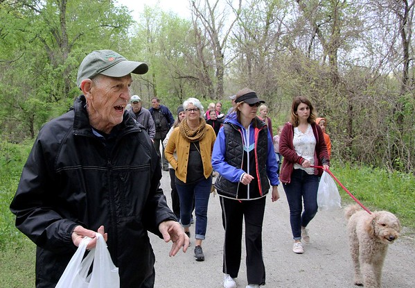 AUSTIN HOUGH | THE GOSHEN NEWS<br /> John J. Smith, a retired science teacher, shows a group of people - and one furry friend - different types of plants and flowers that grow along the Pumpkinvine Nature Trail in Goshen Monday. The trail stretches from Goshen to Shipshewana and features hundreds of different plant species along the path.