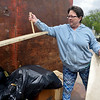 BEN MIKESELL | THE GOSHEN NEWS<br /> Anita Albaugh, Elkhart, tosses wooden shelves into a pile Thursday during Beautify Goshen Week at the Goshen Street Department. Albaugh was helping her mother, Carolyn Cregier, Goshen, clean out clutter in her home.