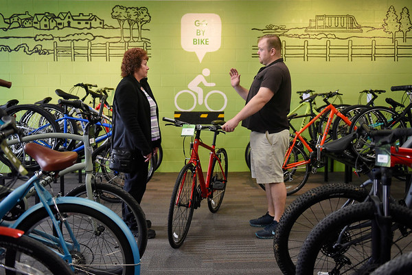 BEN MIKESELL | THE GOSHEN NEWS<br /> Jacob Jones, right, shows a bicycle to Joette Van Hook, Goshen, as she looks for a new purchase Thursday at Lincoln Avenue Cycling in Goshen.