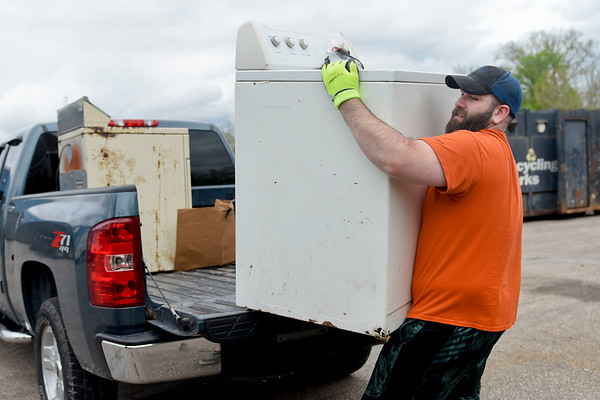 BEN MIKESELL | THE GOSHEN NEWS<br /> James Abney, Goshen, lifts appliances off his truck while getting rid of junk Thursday during Beautify Goshen Week at the Goshen Street Department.