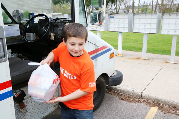 AIMEE AMBROSE | THE GOSHEN NEWS<br /> Michael Aimone (center) carries a bag of frood from a postal truck to the family van at the Aspen Meadows apartment complex in Goshen as he, his sister Olivia  and mother Erica volunteer to collect donations as part of the annual Stamp Out Hunger food drive Saturday.