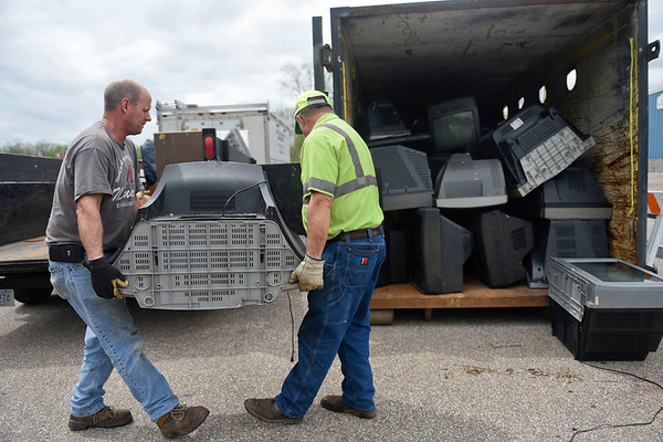 BEN MIKESELL | THE GOSHEN NEWS<br /> Rick Kauffman, Goshen, left, and equipment operator Todd Turner, lift a television as they transport it to the dumpster Thursday during Beautify Goshen Week at the Goshen Street Department. Kauffman was one of many Goshen residents to stop by the Street Department to unload old appliances and other large items to be recycled or thrown away.