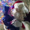 Joseph Weiser | The Goshen News<br /> Amaryllis Rollins, 2, of Syracuse tells Santa Clause played by Dave Schwartz of Syracuse her Christmas wishes during the Syracuse Christmas tree lighting ceremony at Veteran's Memorial Park at Crosson Mill Saturday.