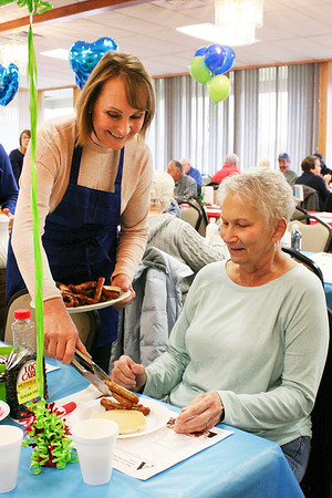 Karen Smith, Elkhart, serves sausage links to Pam Elliott of Goshen during the 56th annual Salvation Army Pancake Day.