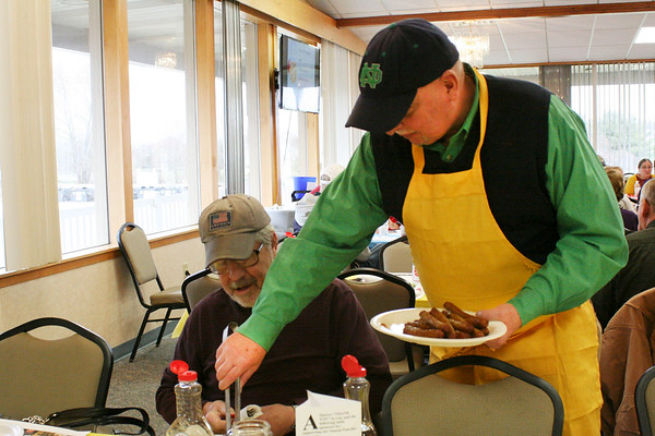 Al Mackowiak serves sausages to Dave Miles, Goshen, at the Salvation Army's Pancake Day.