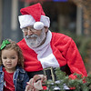 Kamrie Fox, 3, of Nappanee sits with Santa Claus Sunday afternoon along Main Street in Goshen during the annual Holiday Open House, organized by the Goshen Chamber of Commerce and the Downtown Economic Improvement District.