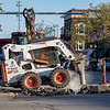 Joseph Weiser | The Goshen News<br /> Nick Hornish of the Goshen City Water Department uses a Bobcat to break up the asphalt to install a new waterline valve to relocate the fire hydrant on the corner of W. Lincoln Ave. and Main St. do to being a pedestrian hazard Monday.