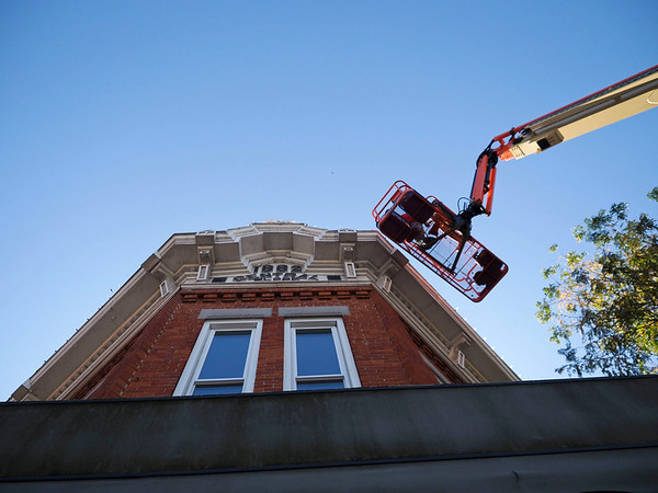 Joseph Weiser | The Goshen News<br /> Signtech employee Tod Lehman of Goshen installs the first set of 10,000 new led Christmas lights on the roof of L&M Hair Design to replace the lights damaged by a major hail storm back in June on Monday.