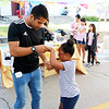 AIMEE AMBROSE | THE GOSHEN NEWS <br /> Adrian Rosas, Goshen, dances with his niece, Olivia Cherry, 7, Goshen, while attending the fourth annual Salsa Festival at the Goshen Farmers Market, 212 W. Washington St., Saturday.