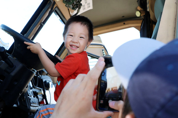 AIMEE AMBROSE | THE GOSHEN NEWS <br /> Alan Jiang, 2, smiles as father, Meng Jiang of South Bend, takes a photo of him behind the wheel of the Elkhart County Regional SWAT vehicle during Touch A Truck at Faith United Methodist Church along C.R. 18 Saturday. The event let children climb into and explore a vareity of vehicles, including fire trucks, police vehicles, construction equipment, tow trucks and public service trucks, as well as the MedFlight emergency helicopter from Memorial Hospital of South Bend.