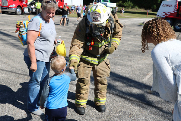 AIMEE AMBROSE   THE GOSHEN NEWS <br /> Brantley Hoover, 3, Granger, shakes the hand of Deputy Chief Brian Jaenichen of the Concord Township Fire Department during Touch a Truck at Faith United Methodist Church along C.R. 18 Saturday. Jaenichen was in full gear, showing children and families what firefighters wear during fires. The event let children climb into and explore a vareity of vehicles, including fire trucks, police vehicles, construction equipment, tow trucks and public service trucks, as well as the MedFlight emergency helicopter from Memorial Hospital of South Bend.