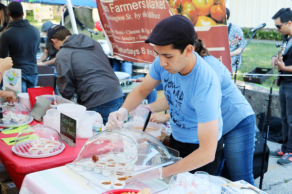 AIMEE AMBROSE   GOSHEN NEWS <br /> Jose Chiquito of Goshen Farmers Market adds more samples of salsa from Los Primos restaurant to one of the tables where salsas from local eateries were available for people to try during the fourth annual Salsa Festival at the farmers market, 212 W. Washington St., Saturday.