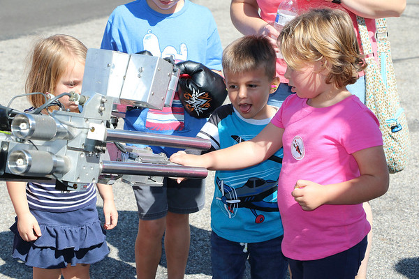 """AIMEE AMBROSE   THE GOSHEN NEWS <br /> Weston Cox, 4, (center) and Lucy Baugtinheimer, 4, (right) shake the """"hand"""" of the Elkhart Police Department's bomb squad robot during Touch a Truck at Faith United Methodist Church along C.R. 18 Saturday. The robot was operated by Elkhart Police Cpl. Jared Davies. The event let children climb into and explore a vareity of vehicles, including fire trucks, police vehicles, construction equipment, tow trucks and public service trucks, as well as the MedFlight emergency helicopter from Memorial Hospital of South Bend."""