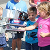 "AIMEE AMBROSE | THE GOSHEN NEWS <br /> Weston Cox, 4, (center) and Lucy Baugtinheimer, 4, (right) shake the ""hand"" of the Elkhart Police Department's bomb squad robot during Touch a Truck at Faith United Methodist Church along C.R. 18 Saturday. The robot was operated by Elkhart Police Cpl. Jared Davies. The event let children climb into and explore a vareity of vehicles, including fire trucks, police vehicles, construction equipment, tow trucks and public service trucks, as well as the MedFlight emergency helicopter from Memorial Hospital of South Bend."