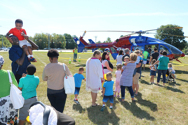 AIMEE AMBROSE   THE GOSHEN NEWS <br /> Families line up to see inside the MedFlight emergency helicopter from Memorial Hospital of South Bend as part of Touch A Truck at Faith United Methodist Church along C.R. 18 Saturday. The event let children climb into and explore a vareity of vehicles, including fire trucks, police vehicles, construction equipment, tow trucks and public service trucks, as well as MedFlight.