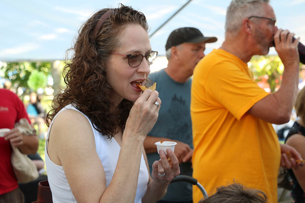 AIMEE AMBROSE | THE GOSHEN NEWS <br /> Ingrid Friesen-Moser samples salsa from Los Primos restaurant while attending the fourth annual Salsa Festival at Goshen Farmers Market, 212 W. Washington St., Saturday.