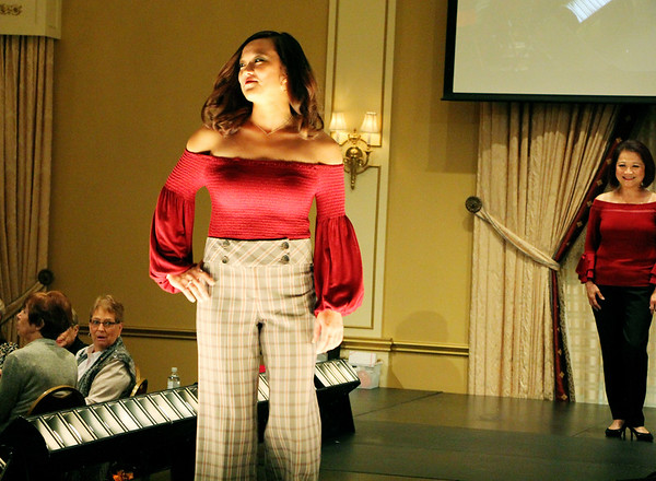 AIMEE AMBROSE | THE GOSHEN NEWS <br /> Gaby Nguyen strikes a pose while Francoise Nguyen (right) looks on. The two modeled together during the 2019 Fashion Show, which served as a fundraiser for Cancer Resources for Elkhart County at the Lerner Theatre in Elkhart Wednesday.