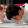Roger Schneider | The Goshen News<br /> Kaitlyn Hughes keeps an eye on her competition, Santiago Zquala, during the pie eating contest at the Nappanee Apple Festival Saturday. Competitors were timed on how fast they could eat a piece of pie without the use of their hands. Zquala took first place.