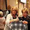 AIMEE AMBROSE | THE GOSHEN NEWS <br /> Women examine apparel on display ahead of the 2019 Fashion Show, a fundraiser for Cancer Resources for Elkhart County at the Lerner Theatre in Elkhart Wednesday.