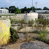Roger Schneider | The Goshen News<br /> Weeds and wildflowers grown in the rubble that was once the Johnson Controls office building. Storage tanks from a previous cleanup effort are in the background. Neighbors of the former factory were Tuesday night presented with a plan to continue the cleaning of the site.
