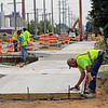 Roger Schneidier | The Goshen News<br /> Ed Jones of South Bend puts the finishing touches on freshly-poured concrete along Ninth Street in Goshen Monday. The city government is having the Ninth Street corridor improved, which includes the pedestrian/bicycle trail that Jones is working on. Other changes include parking and landscaping.