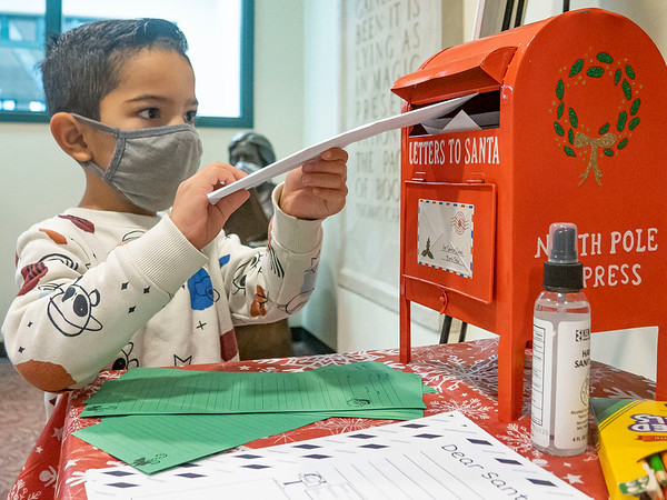 Mateo Horta, 4, son of Mio Horta and Stephanie Benton, drops his letter into Santa's mailbox at the Goshen Public Library. Mateo attends Walnut Hill Early Childhood.