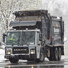 A Borden garbage truck driver makes a right turn onto Main Street from East Garfield Avenue in Goshen on a snow filled Friday afternoon.