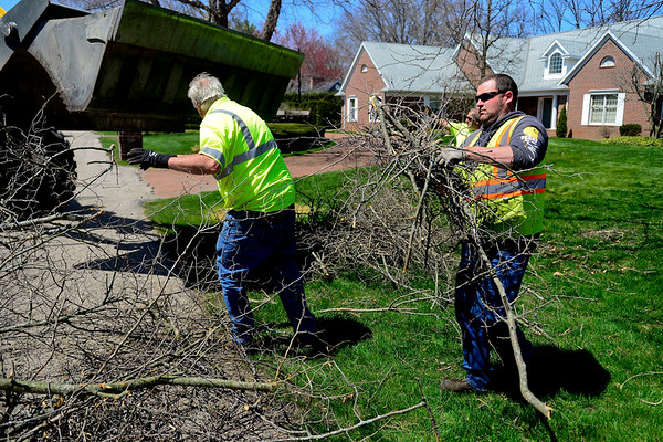 THE GOSHEN NEWS<br /> In this March 30, 2018 file photo, Matt Beard, right, with the Goshen Street Department carries branches while cleaning up brush along Carter Road in Goshen. The City Council is considering new rules and fines for the collection service.