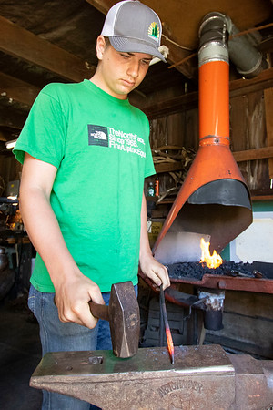 Blacksmith student Quinn Klopfensten uses a hammer to pound an iron rod into a fire poker Wednesday at Blacksmith James Rubley's shop in Shipshewana.