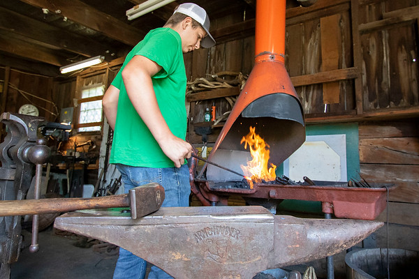 Blacksmith student Quinn Klopfensten inserts an iron rod into a blacksmithing   forge Wednesday at Blacksmith James Rubley's shop in Shipshewana.